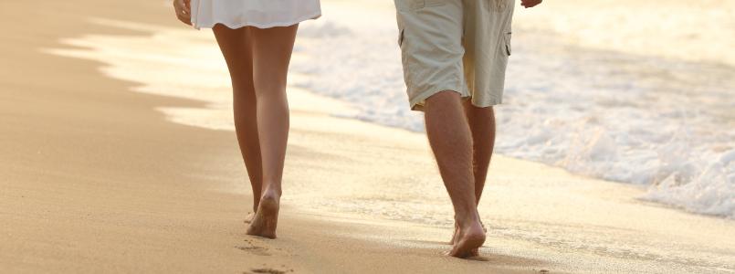 Zwei Menschen gehen am Strand - Gehmeditation